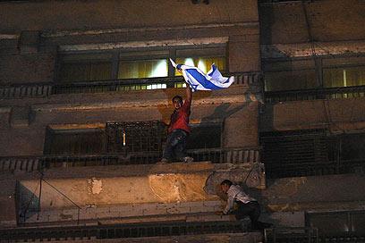 מפגין עם דגל ישראל בבניין השגרירות (צילום: AP)