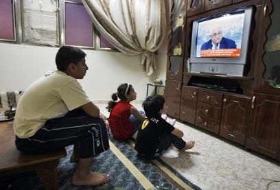 פלסטינים צופים בנאום אבו מאזן, אתמול ברמאללה (צילום: AFP)