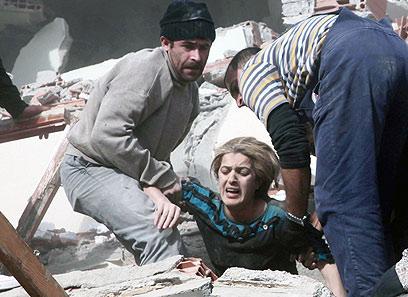 מחלצים אישה שנקברה תחת ההריסות ברעש האדמה (צילום: AP)