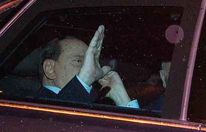ברלוסקוני מנופף לעיתונאים בעוזבו את בית הנשיא (צילום: AP)