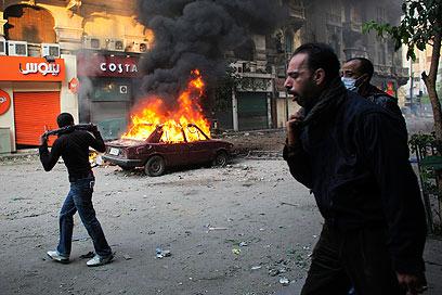מכונית עולה באש ליד כיכר א-תחריר, היום (צילום: AP)