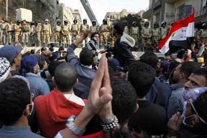 מפגינים מול חיילים בכיכר (צילום: EPA)