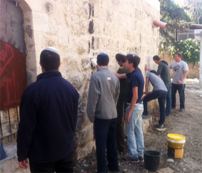 """הצעירים מנקים את קירות המסגד. """"מוחקים כתם"""" (צילום: עמיחי בן סעדון)"""