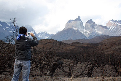 גם זו אטרקציה. תייר מצלם את השריפה (צילום: AFP)