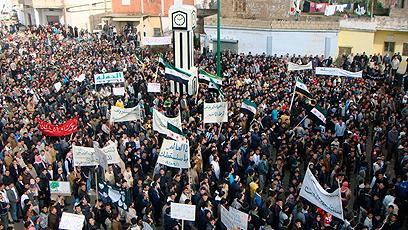 אזרחים סורים מפגינים נגד משטר אסד בעיר חולה, ליד חומס (צילום: רויטרס)