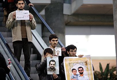 המפגינים עם תמונותיו של אחמדי-רושאן (צילום: AP)