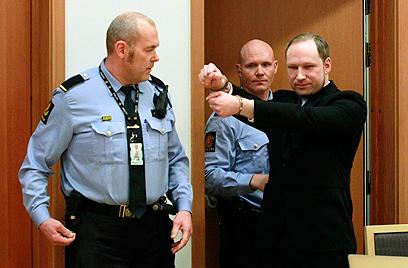 """""""ברכת שלום של הימין הקיצוני"""". ברייויק מותח ידיו בבית המשפט (צילום: AP)"""
