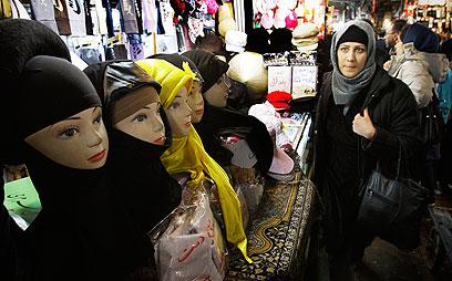 חיי היום יום נפגעו בעקבות הסנקציות. דוכן לממכר כיסוי ראש בטהרן (צילום: AP)