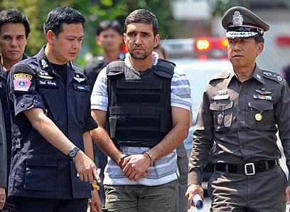 אחד העצורים האיראנים מובא לשחזור בבנגקוק (צילום: AFP)