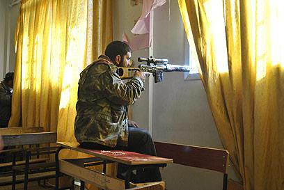 מורד סורי דרוך בעיר חומס (צילום: AP)