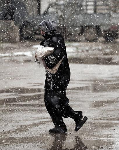 קופאים מקור. שלג בחומס (צילום: AFP)