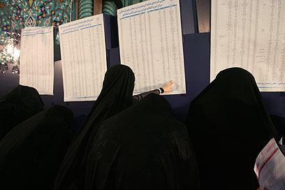בודקים למי להצביע (צילום: MCT)