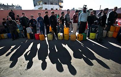"""""""מהדיאלוגים לא יצא דבר"""". תושבי עזה בתור לחלוקת דלק (צילום: EPA)"""