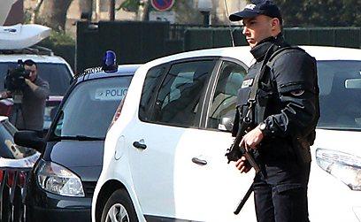 שוטר ליד השיירה בפריז בה נסע אחיו של המחבל (צילום: AFP)