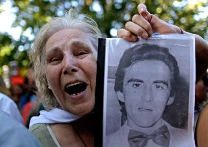 מפגינה מול האולם שבו נערך משפטו של ראש החונטה לשעבר (צילום: AP)