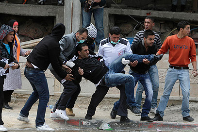 מפנים פצוע פלסטיני בקלנדיה (צילום: רויטרס)
