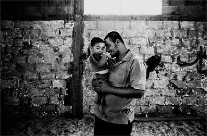 """אחמד, בן 27, עם בנו. אחמד הוא חבר בגדודי עז א-דין אל-קסאם, הזרוע הצבאית של חמאס. הוא לוחם. ב-26 ביולי, 2008, הוא נפצע קשה בפעולה ישראלית והיה על סף מוות. אף על פי כן הוא רוצה להמשיך להילחם. """"ארצנו כבושה וזוהי זכותו של כל אחד להתנגד לכיבוש"""" (צילום: פרדריק סוטרו)"""