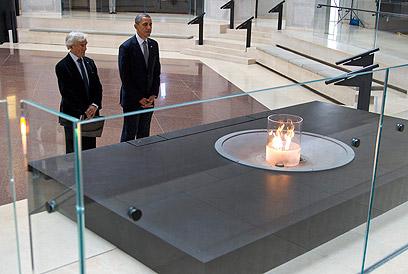 """אובמה וויזל במוזיאון. """"לעולם לא אשכח מה שראיתי אני בבוכנוולד, היכן שכה רבים מתו כשהמילים 'שמע ישראל' על שפתותיהם"""" (צילום: AP)"""