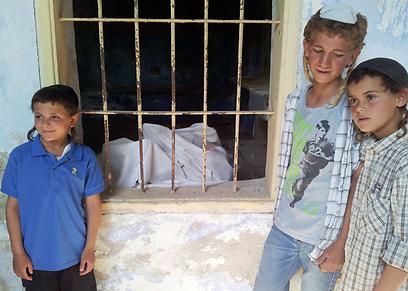 """הנערים ליד הבית הנטוש (צילומים: אתר חב""""ד, שטורעם.נט)"""