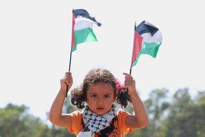 """""""עם שעבר טיהור אתני ב-48'"""". מפגינה צעירה סמוך לאום אל-פחם (צילום: ג'ורג' גינסברג)"""