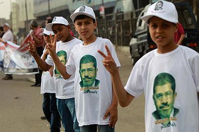 גם הילדים צועקים שמות מועמדים. תומכי מוחמד מורסי (צילום: AFP)