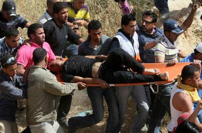 הפלסטיני הפצוע מפונה מהמקום. היורה לא נעצר (צילום: AFP)