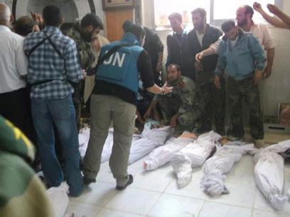 """פקחית האו""""ם בוחנת את הגופות בחולה (צילום: רויטרס)"""