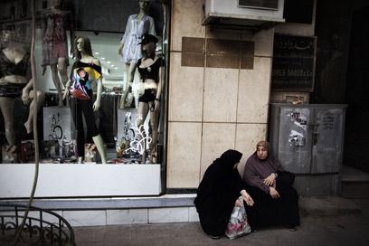 נשים מצריות בלבוש מסורתי ליד חנות בגדים (צילום: AFP)