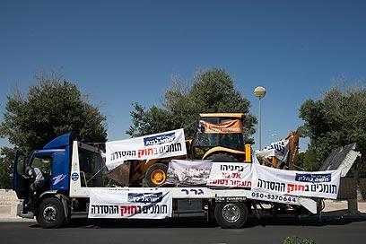 הטרקטור והשלטים שהביאו המפגינים הבוקר לירושלים (צילום: אוהד צויגנברג)