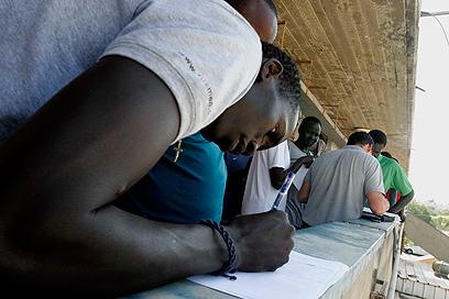 """אזרח דרום סודן חותם על """"עזיבה מרצון"""" (צילום: אליעד לוי)"""