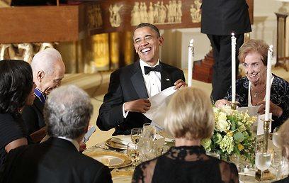 אובמה עושה צחוקים בשולחן, כשלימינו פרס ואשתו מישל (צילום: רויטרס)