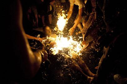 המצית בוער והמפגינים ממהרים לכבות אותו (צילום: AFP)