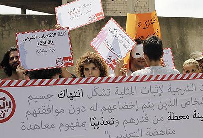 """מפגינה נגד הבדיקות. """"125 אלף לירות לבנוניות"""" (צילום: AFP)"""