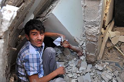יד מבצבצת מבין ההריסות (צילום: AFP)