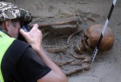 בסוף, נכנע לעינויי הקומוניסטים. ארכיאולוג מתעד את אחד השלדים (צילום: AP)