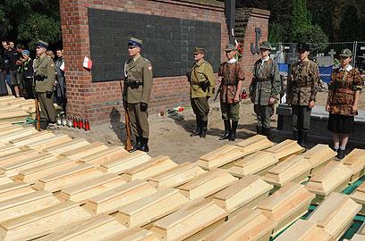 חיילי צבא פולין חולקים כבוד לגיבורים ששרידיהם בארונות (צילום: AP)