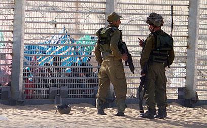 חיילים ליד קבוצת המסתננים בגבול. נותנים להם מים (צילום: AP)
