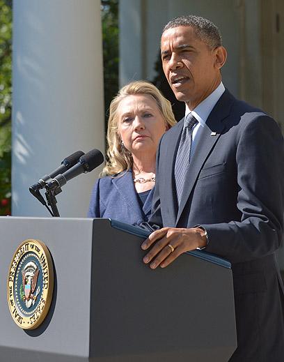 """אובמה וקלינטון, הערב. """"החופש שלנו נשמר בזכות אנשים שמוכנים להילחם עבורו ולפעמים להקריב את חייהם"""" (צילום: AFP)"""