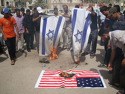 Protesters burn flags in Iraq (Photo: AFP)