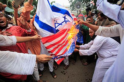 """מחאה עולמית. דגלי ארה""""ב וישראל עולים באש בבנגלדש (צילם: רויטרס)"""