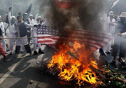 שורפים דגלי ארצות-הברית באינדונזיה (צילום: AP)