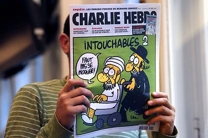 """""""אסור ללעוג"""". יהודי חרדי דוחף מוסלמי על כיסא גלגלים בשער העיתון (צילום: AFP )"""
