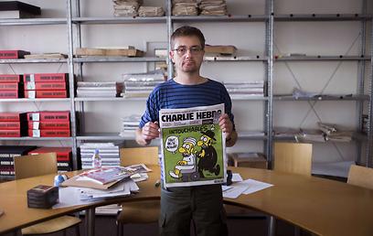 """אבטחה גדולה סביב משרדי העיתון. אחד מעורכי """"שארלי הבדו"""" (צילום: AFP )"""