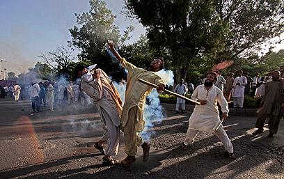 מפגין בפקיסטן זורק מכל גז מדמיע לעבר השוטרים (צילום: AP)