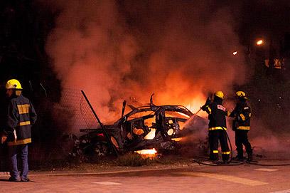 כבאים מכבים את הרכב לאחר הפיצוץ, אמש (צילום: גלעד רדט)