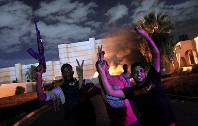 """המפגינים חוגגים לאחר הפשיטה על מחנה """"אנסר אל-שריעה"""" (צילום: AFP)"""
