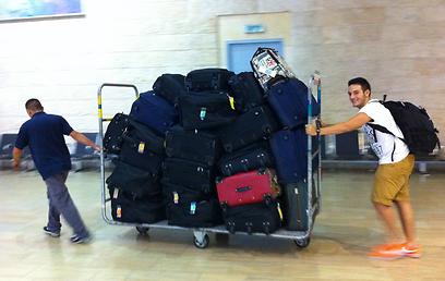 """הבן אייזיק והמזוודות בנתב""""ג. חלק מהציוד נותר במילאנו  (צילום: תרי לוי)"""