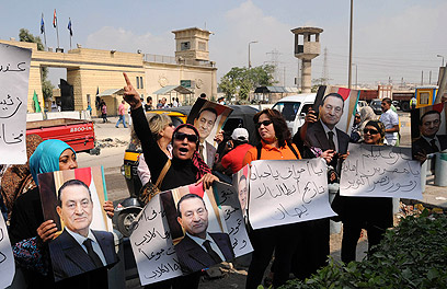 """""""השופטים אמרו את דברם"""". תומכי מובארק מחוץ לכלא טורה בקהיר (צילום: AP)"""