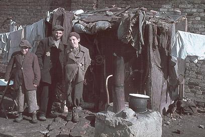 גבר וילדים ליד מחסה מאולתר בגטו קוטנו, 1940 (צילום: Gettyimages)