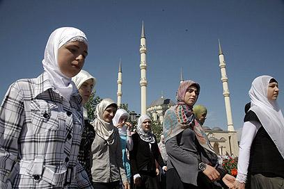 """בצ'צ'ניה יורים כדורי צבע על נשים שלא חובשות כיסוי ראש. תלמידות בי""""ס בגרוזני (צילום: AP)"""